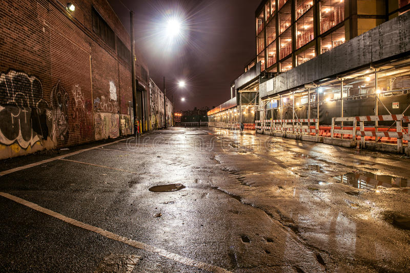 Asfaltowa uliczna droga w nocy mieście po deszczu Parking z graffiti na ściana z cegieł obrazy stock