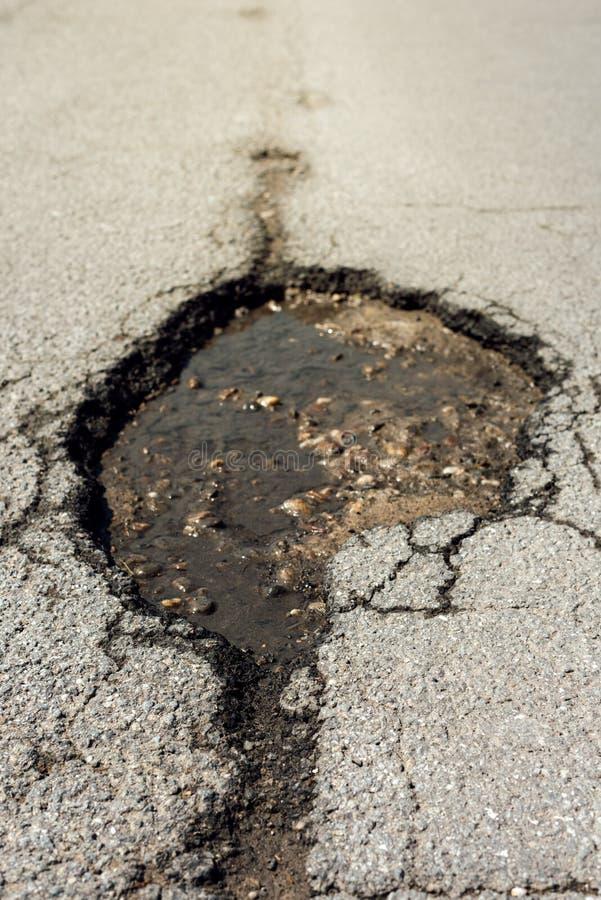 Asfaltowej drogi dziury szkoda zdjęcia stock