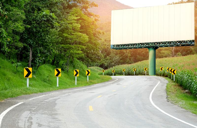 Asfaltowej drogi wyginająca się strona pole uprawne z strzałkowatymi znakami, Duży whi zdjęcia stock
