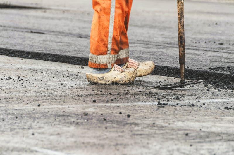 Asfaltowy pracownik z drewnianymi chodakami zdjęcie stock