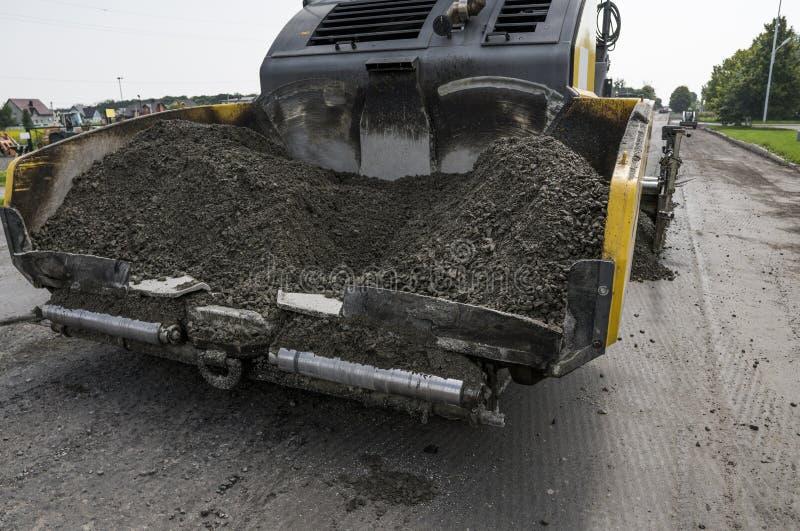 Asfaltpavermaskinen under konstruktion och att reparera för väg fungerar En paverefterbehandlare, en asfaltefterbehandlare eller  royaltyfri foto