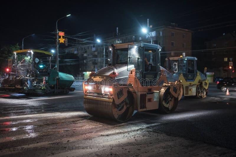 Asfaltstenläggning med vägrullen på natten arkivbilder