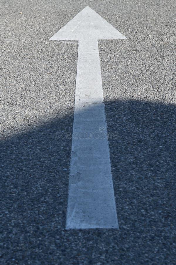 Asfalttecken: vit pil på den konkreta texturen royaltyfria foton
