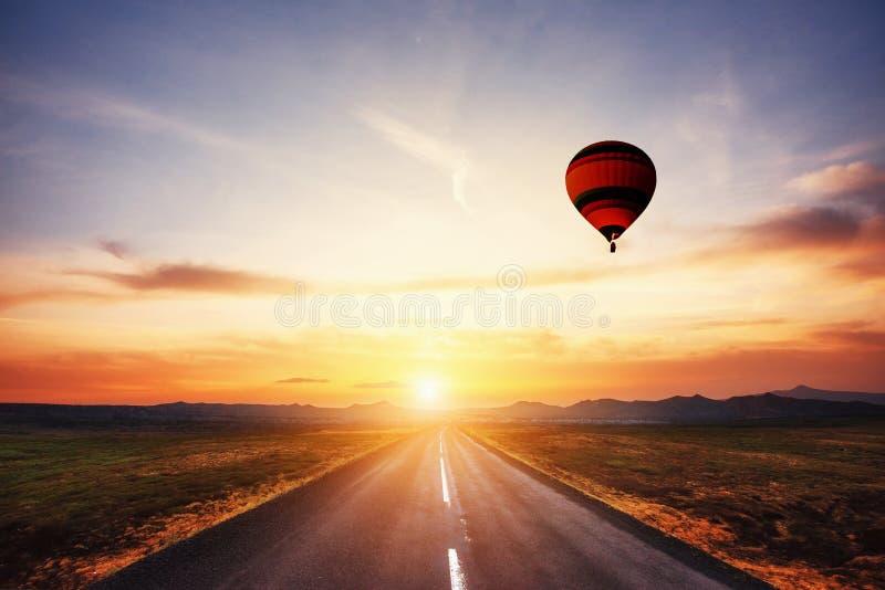 Asfaltväg along och färgad boll i himlen på solnedgången royaltyfria foton