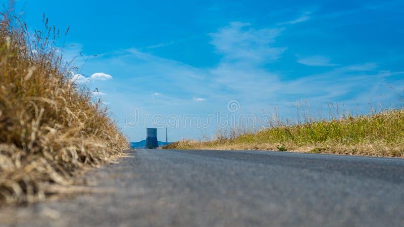 Asfaltväg i ett fält på slutet som är av en enorm lampglas av en kärnkraftverk i Västtyskland på en härlig sommardag, royaltyfri foto