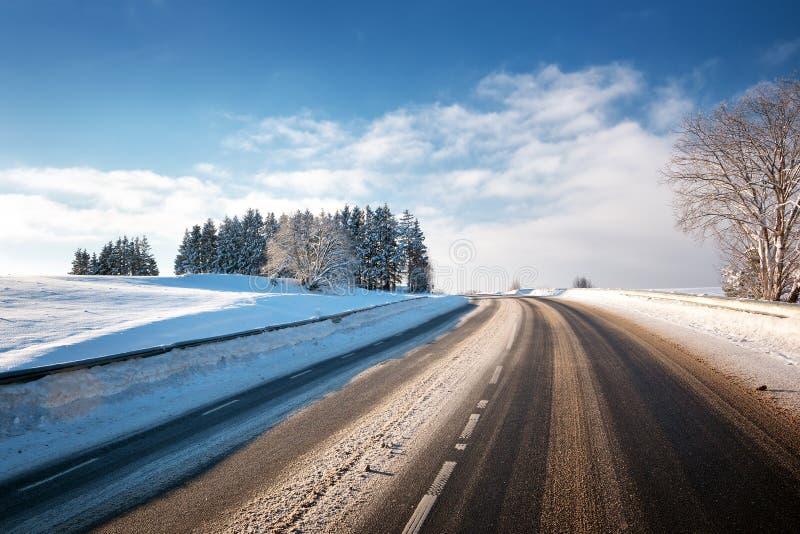 Asfaltväg i snöig vinter på härlig solig dag royaltyfri bild
