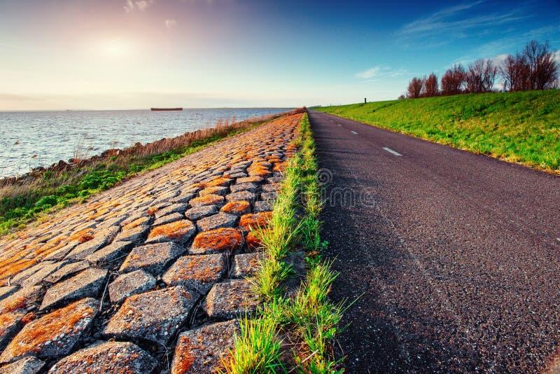 Asfaltväg längs havet på solnedgången arkivfoton
