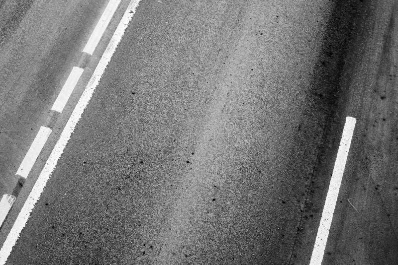 Asfaltväg med delande linjer och gummihjulspår royaltyfri fotografi