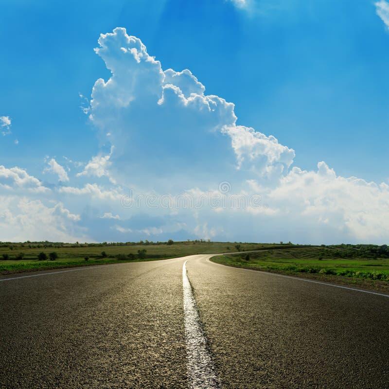 Asfaltväg och molnig himmel arkivbild