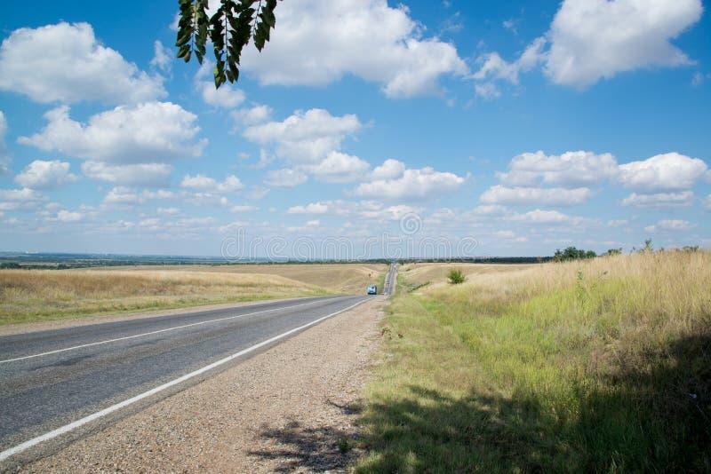 Asfaltväg som går till horisonten på en solig sommardag fotografering för bildbyråer