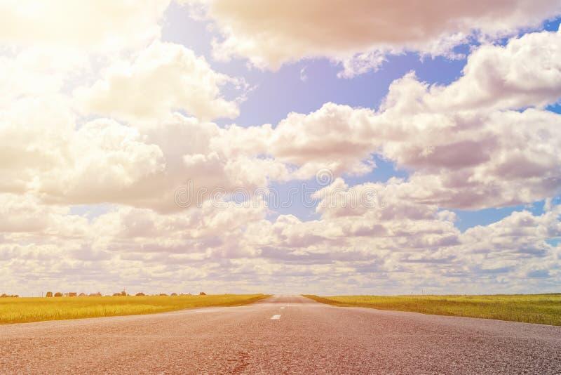 Asfaltväg till och med det gröna fältet och moln på blå himmel i sommardag arkivbild