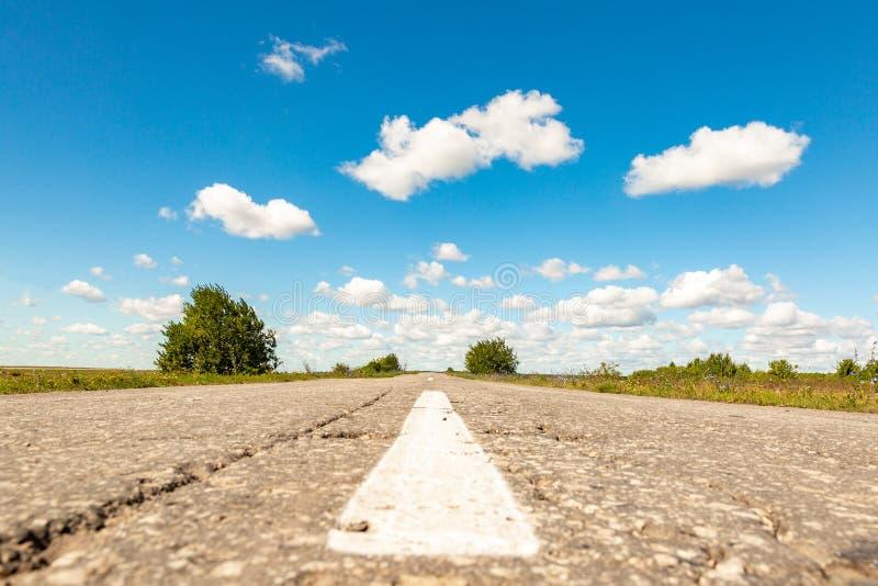 Asfaltväg till och med det gröna fältet och moln på blå himmel i sommardag arkivfoton