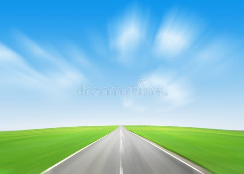 Asfaltväg till och med det gröna fältet och den blåa himlen royaltyfria bilder