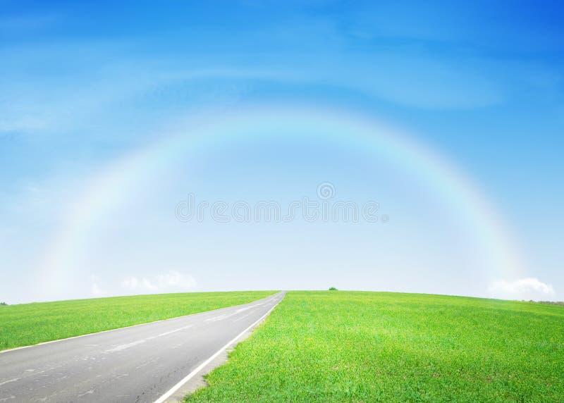 Asfaltväg till och med det gröna fältet och regnbågen fotografering för bildbyråer