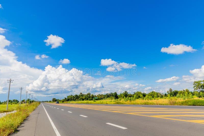 Asfaltvägen kör längs fältet och har en härlig blå himmel fotografering för bildbyråer