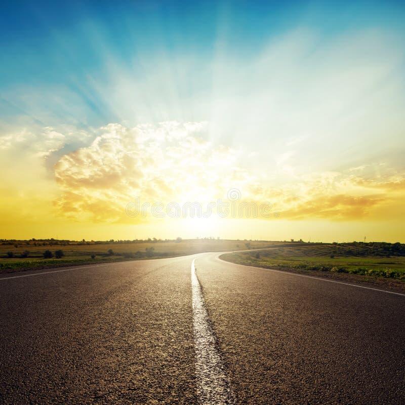 Asfaltweg aan horizon en zonsondergang in wolken royalty-vrije stock afbeeldingen