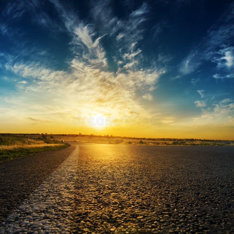 Asfaltweg en goede oranje zonsondergang in wolken royalty-vrije stock afbeeldingen
