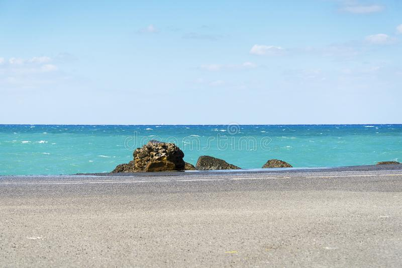 Asfaltweg en overzeese kustlijn met blauwe hemel op horizon Landschap in zonnige de zomerdag stock afbeeldingen