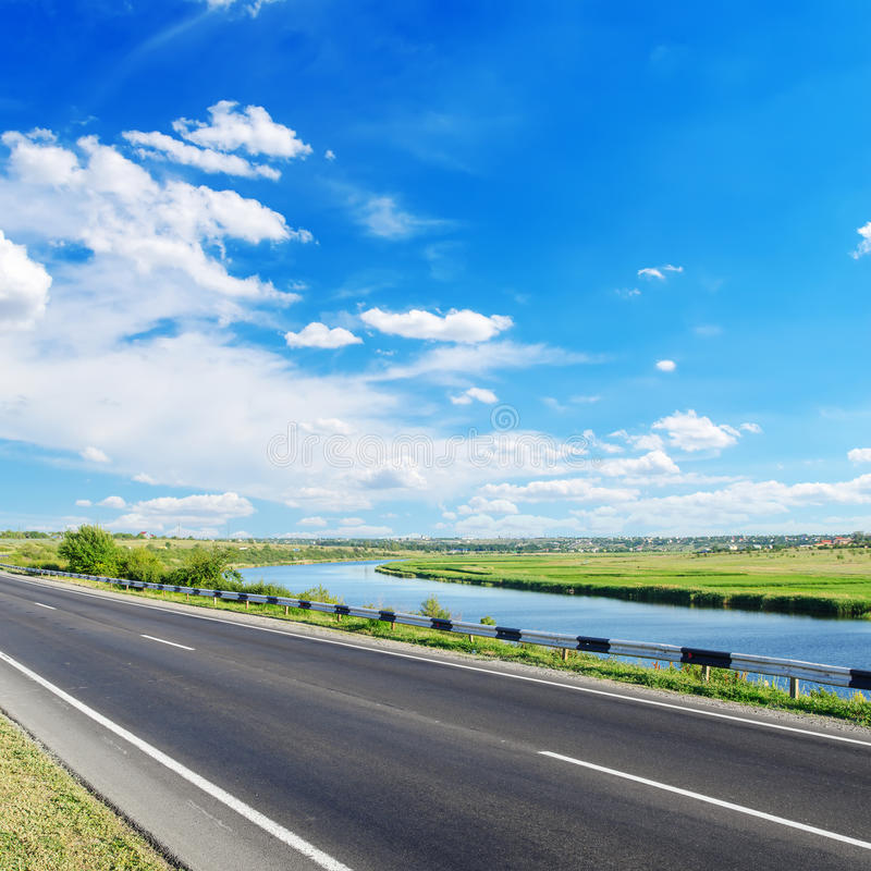 Asfaltweg en rivier langs het met blauwe hemel stock foto's