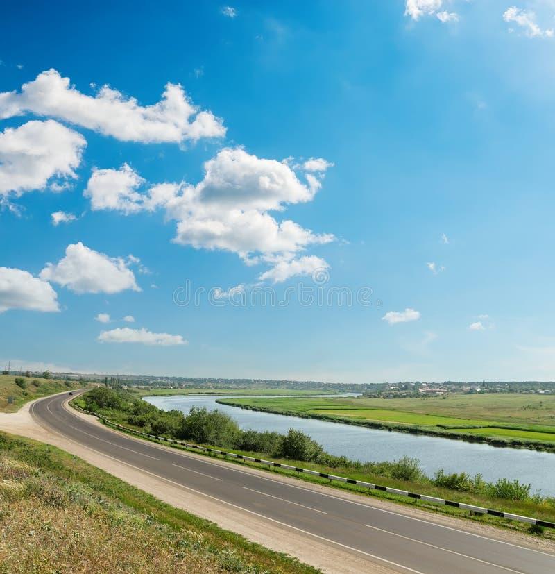 Asfaltweg en rivier onder blauwe hemel met wolken stock foto's