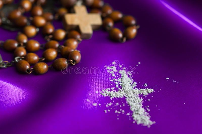 Ash Wednesday religion concept on violet fabric background with rosary. Closeup stock photo