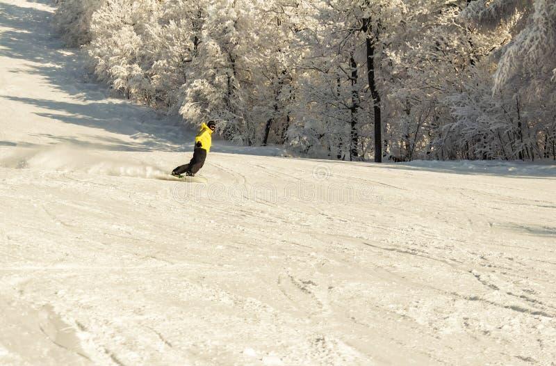 ASHA, R?SSIA - 27 de abril de 2011: o snowboarder desce na inclina??o coberto de neve e faz uma manobra de gerencio, cara n?o ? v fotos de stock royalty free