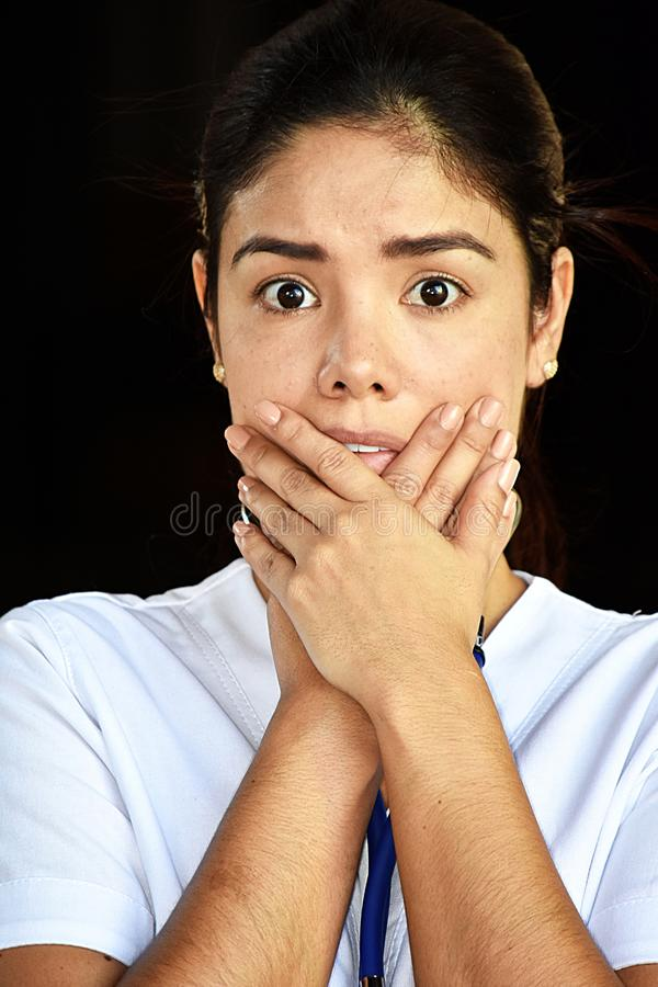 Ashamed Beautiful Female Nurse. A pretty young Colombian adult female royalty free stock image