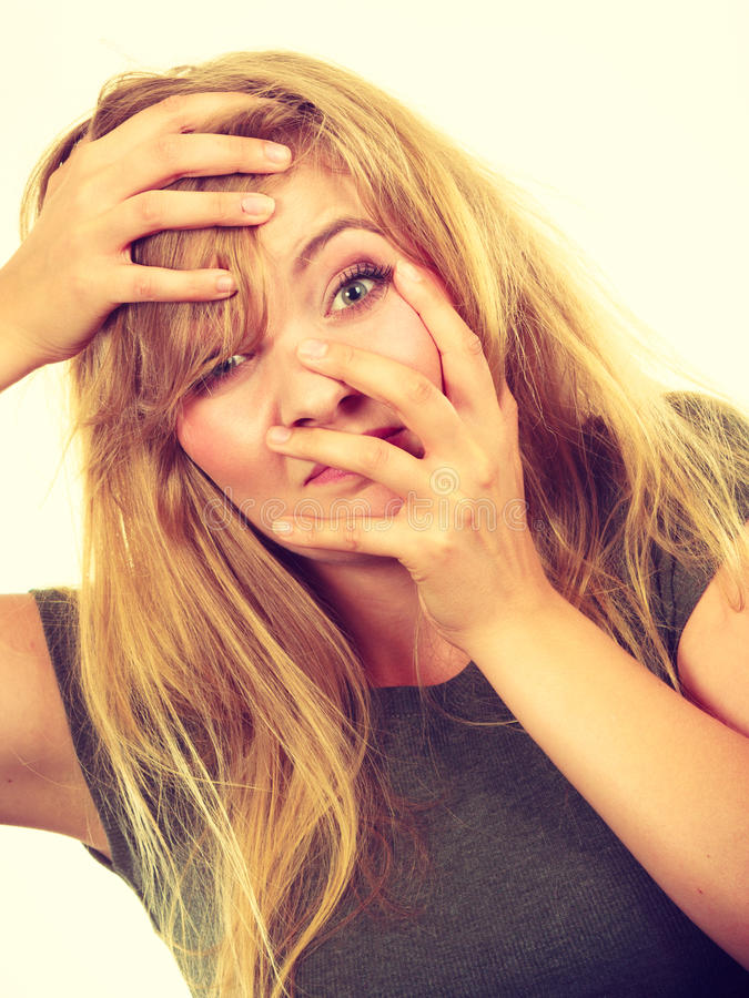 Ashamed embarrassed blonde woman with hands on face royalty free stock photo