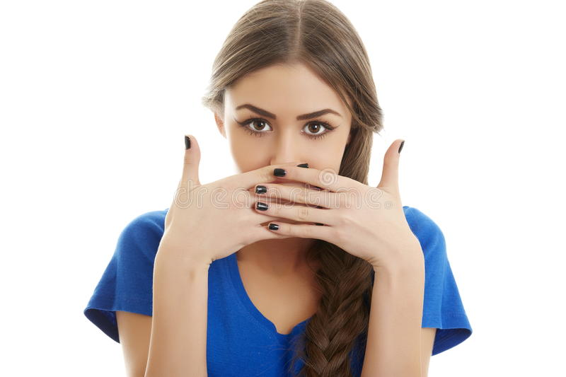 Ashamed woman. Portrait of ashamed young beautiful woman covering her mouth with both hands. Isolated on white background stock photo
