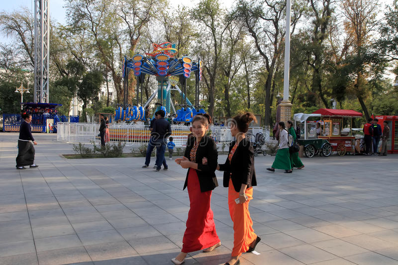 Ashgabad, Turkmenistan - October 10, 2014. Two unidentified young girls in national dress at amusement park of Ashgabad on 10 Oct stock photo