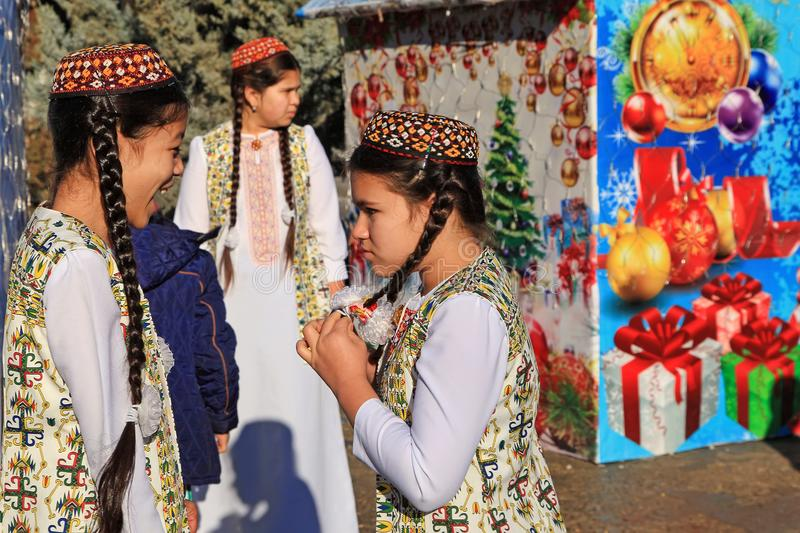 ASHGABAT, TURKMENISTAN - January, 04, 2017: Two unknown young girls in national clothes laugh and talk. ASHGABAT, TURKMENISTAN -. January, 04, 2017 stock photo