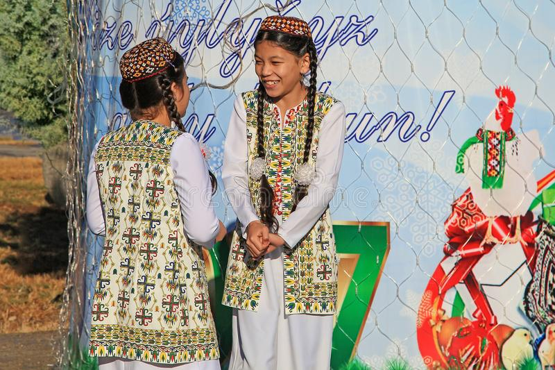 ASHGABAT, TURKMENISTAN - January, 04, 2017: Two unknown young girls in national clothes laugh and talk. ASHGABAT, TURKMENISTAN -. January, 04, 2017 royalty free stock image