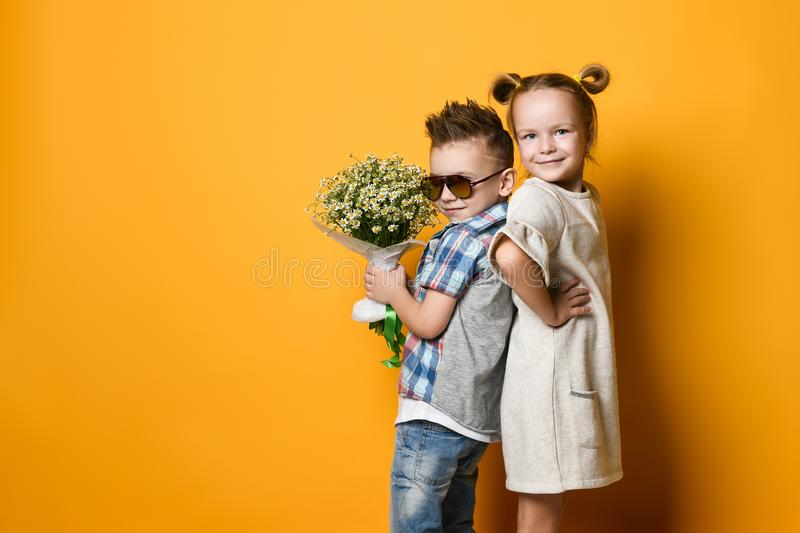 Ashionable little boy and girl in jeans and plaid shirts. stock photo