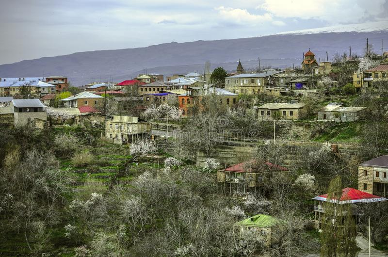 Ashtarak with medieval churches and flowering apricot trees against the background of a darkened sky,among the snow-capped mountai stock images