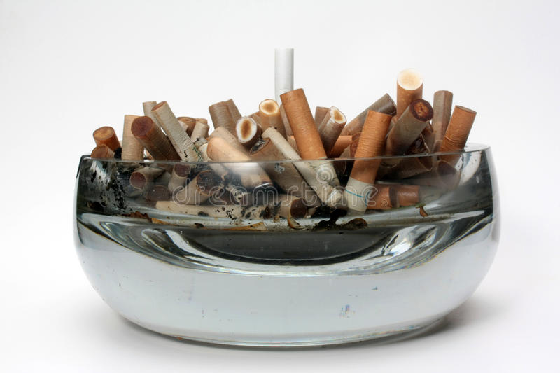 Ashtray. Authentic glass ashtray full of cigarette butt royalty free stock image