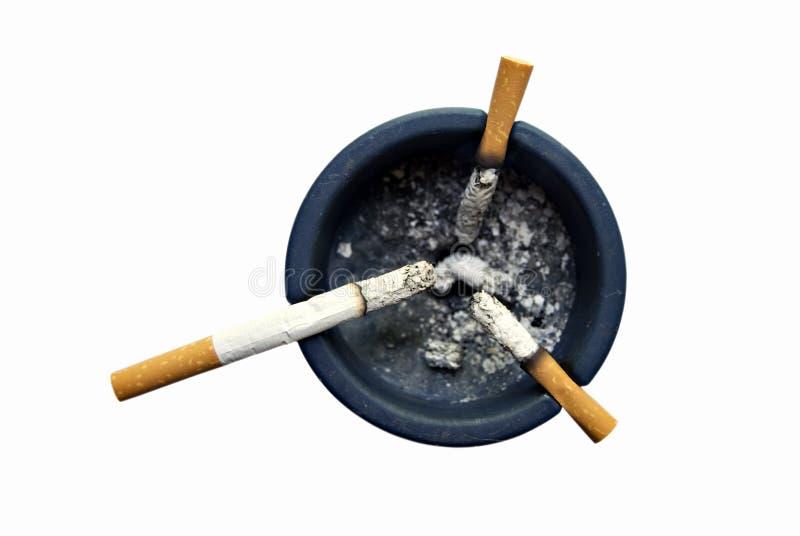 Ashtray. Blue ashtray with three cigarettes royalty free stock image