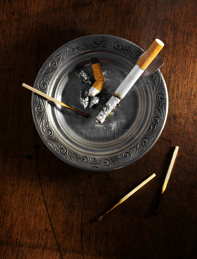 Ashtray. Decorated silver ashtray with cigarette butts and matches over wooden table royalty free stock image