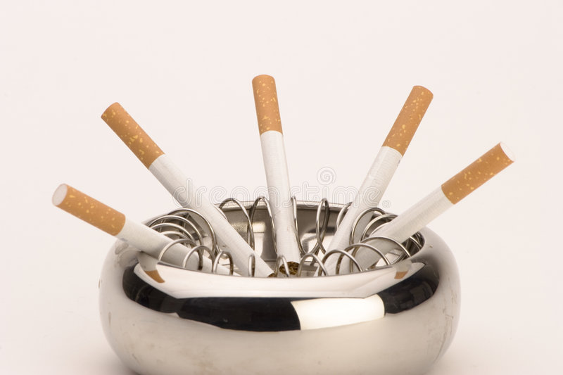 Ashtray with cigarettes. An ashtray with cigarettes against a plain background stock image