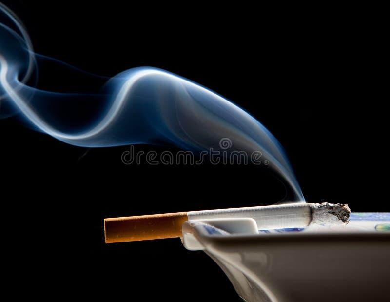 Ashtray and smoke wisp. Cigarette on ashtray with a beautiful wisp of smoke stock image
