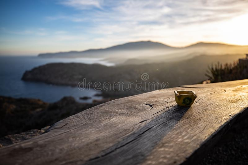 Ashtray on a wooden board with shadow created by the sunset light stock photo