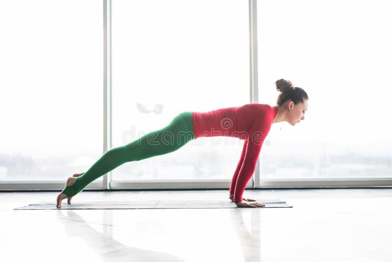Ashva sanchalasana. Beautiful yoga woman practice plank poses in a big window. Hall background. Yoga concept royalty free stock images