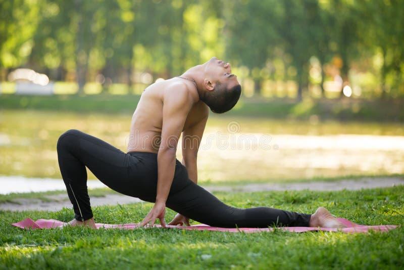 Ashva Sanchalasana (var). Profile of sporty young Indian man practicing yoga, fitness, pilates on riverbank in park, doing low lunge exercise, Ashva Sanchalasana stock photo