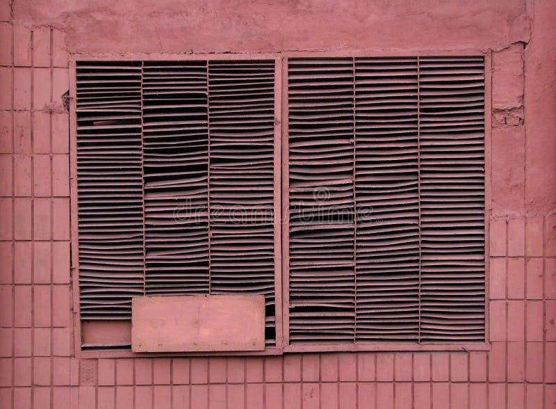 Ashy pink color old closen metal jalousie industrial window. Ashy pink color old closen metal jalousie grid industrial window on panel wall facade stock photos