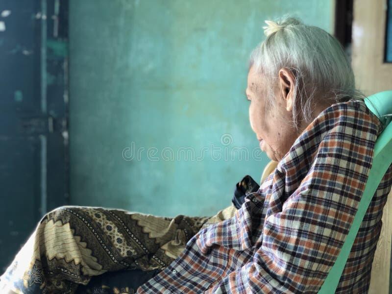 Asiática idoso, mulher do birmanês que situa com pé cruzou-se na cadeira plástica verde e em olhar na distância fotografia de stock royalty free