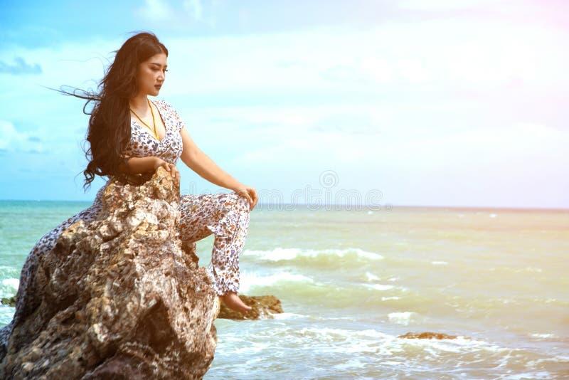 Asiática, mais gordura e mulher com excesso de peso em vestidos brancos sentados na rocha na praia foto de stock