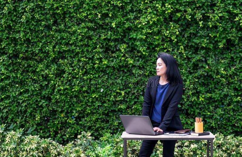 Asiático Busineswoman que usa o laptop que trabalha fora do escritório fotografia de stock