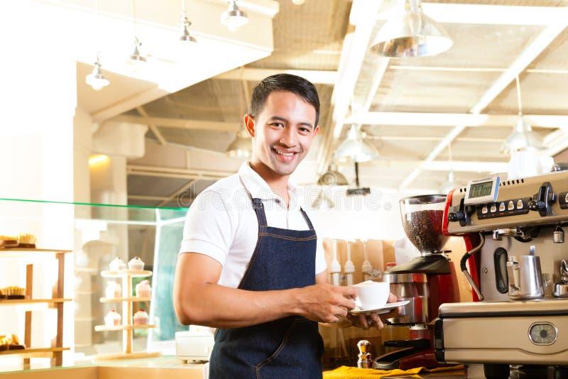 Asiático Coffeeshop - o barista apresenta o café imagem de stock