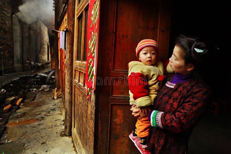 Asiático con el bebé en sus brazos, soportes en la calle rural. foto de archivo