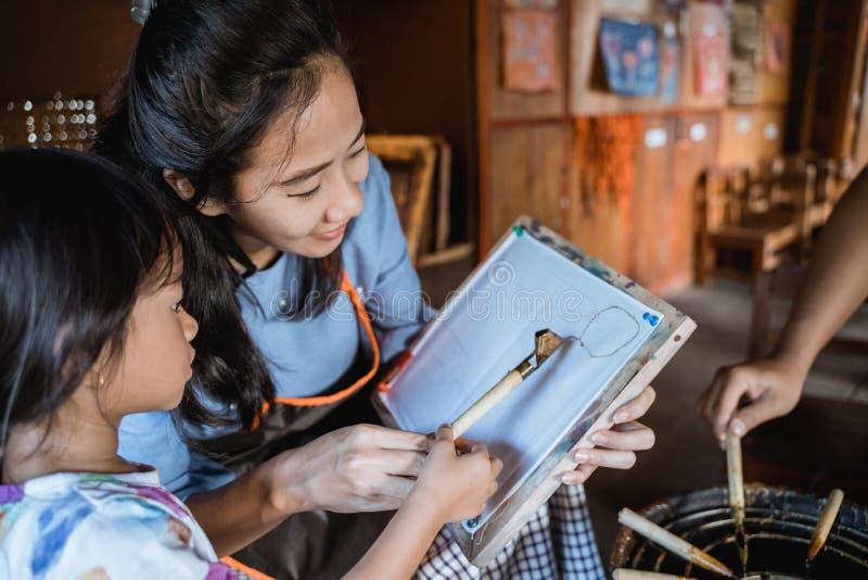 Asiático da mãe e da criança que faz o teste padrão do batik foto de stock