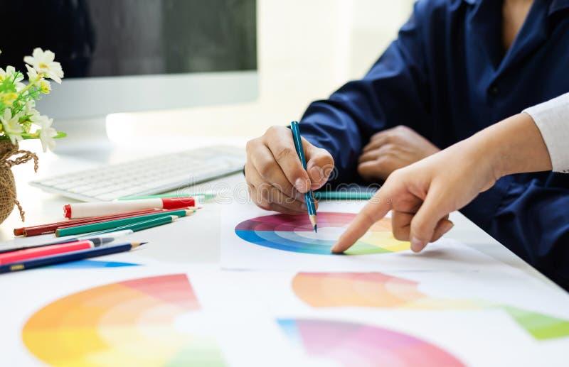 Asiático do designer gráfico que trabalha junto o conceito das ideias do editor do projeto do ux das amostras de folha da cor imagem de stock royalty free